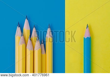 One Blue Pencil On Yellow Background And Group Of Yellow Pencils On Blue Background. Individuality A