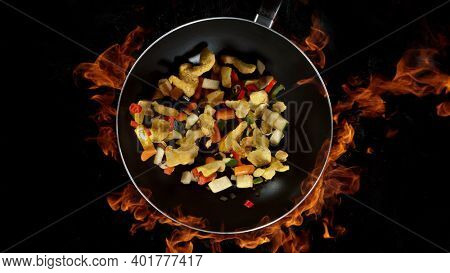 Asian chicken mix in wok pan, flames on background. High angle view of meat preparation, studio shot.