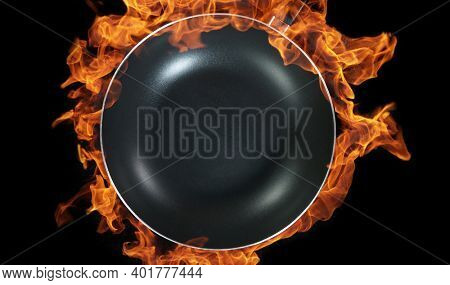Empty wok pan, flames on background. High angle view of meal preparation, studio shot.