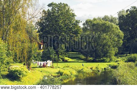 Rural House Among Trees By The River With Boats. Clothes Are Dried On The Clothesline On A Sunny Aut
