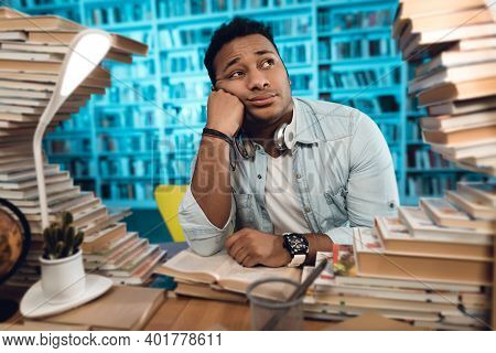 Ethnic Indian Mixed Race Guy Sitting At Table Surrounded By Books In Library. A Man Sits Surrounded