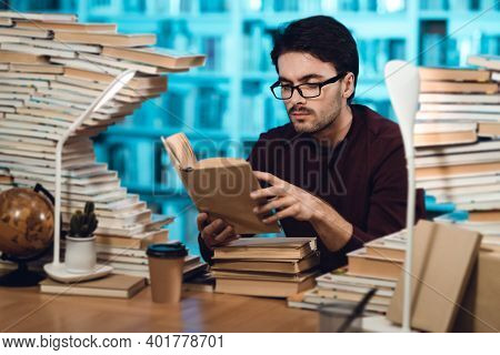 White Guy Surrounded By Books In Library. Student Is Reading Book.