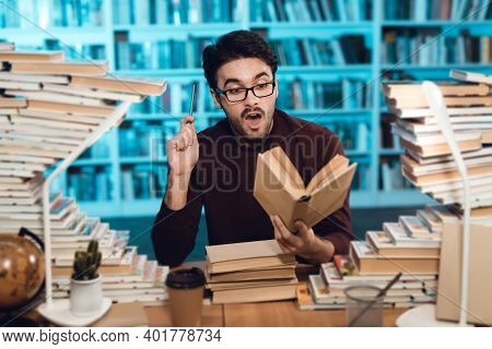 White Guy Surrounded By Books In Library. Student Is Emotionally Reading Book.