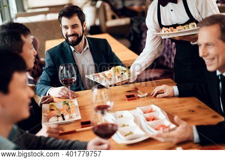 Close Shot Of People Clinking Glasses Of Wine. Adult Businessmen Sit At A Table And Drink Wine With