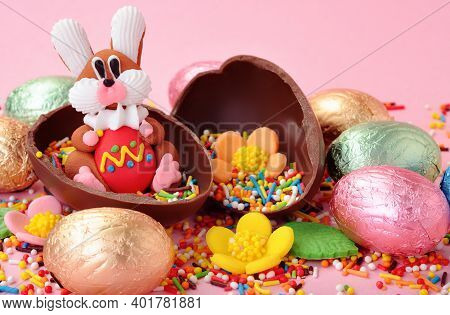 Small Sweet Bunny And Chocolate Eggs In Shiny Colored Foil Wrapper Around On Pink Background. Easter