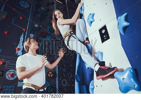 The Girl Looks Down While Climbing The Wall For Climbing. A Man Insures A Girl Who Climbed High On A