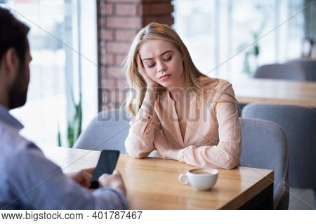 Bored Young Woman Annoyed At Her Boyfriend Playing Games On Smartphone At City Cafe. Millennial Guy