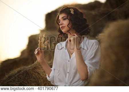 Young Beautiful Girl In A Straw Hat In A Rustic Style Sits Resting In The Countryside On An Old Wood