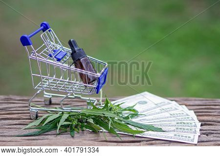 Shopping Trolley With Cannabis Oil Extracts In A Jar, Placed On Wooden Table, Cannabis Leaves, And M