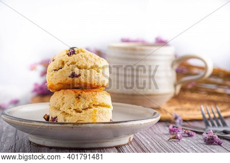 Close-up Of Traditional British Scones On A Plate With A Tea Cup And Flower Blurred Background. Spac