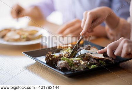 Cropped View Of Millennial Couple Eating Tasty Meat And Vegetable Salad At Table In Cafe. Closeup Of