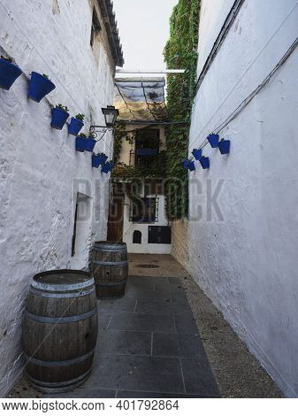 Blue Flowerpots Decoration Hanging On White Wall Of Narrow Lane Alley With Wooden Barrel Cask In Cor