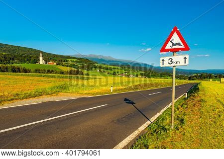 An Austrian Rural Landscape With An Empty Road Between Agricultural Fields Leading To The Alps, A Sm