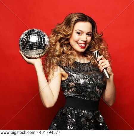 Party, holiday and celebration concept:Young blond woman with long wavy hair dressed in evening dress holding a microphone and disco ball, singing and smiling over red background