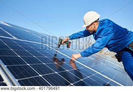 Male Engineer In Blue Suit And Protective Helmet Installing Stand-alone Solar Photovoltaic Panel Sys
