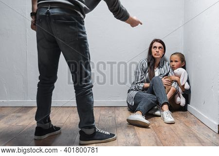 Child With Toy And Woman With Bruises Sitting On Floor Near Abusive Husband Pointing With Finger On