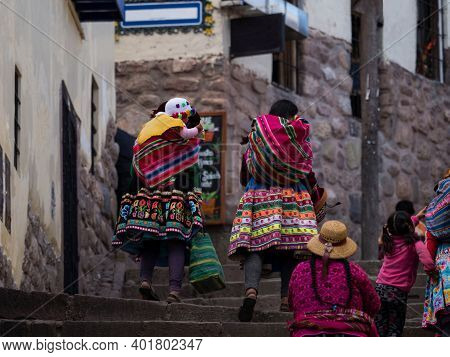 Indigenous Quechua Women In Traditional Colorful Handwoven Textile Clothing Dress Costume Walking In