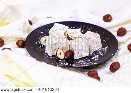 Traditional Turkish Delight Sweet Homemade Rahat Lokum With Hazelnuts And Sugar Powder On Black Plat
