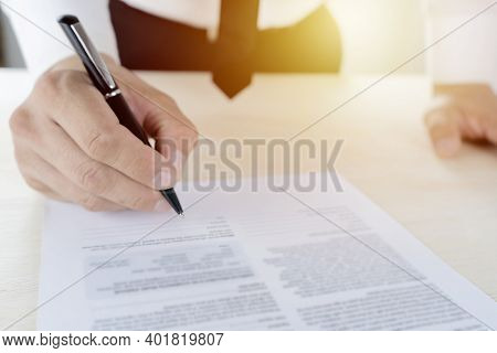 Businessmen Are Signing Contracts. Wearing A White Shirt Black Slacks, Black Tie, Dignified Look, Co