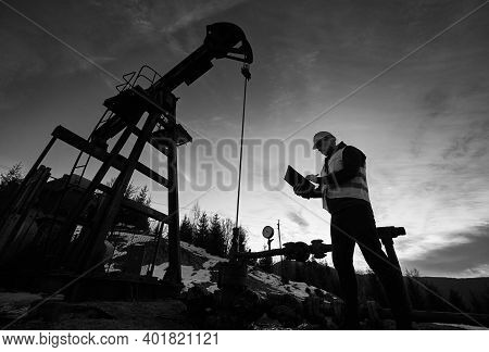 Low Angle Of Petroleum Engineer Looking At Oil Pump Rocker-machine And Writing On Clipboard. Silhoue
