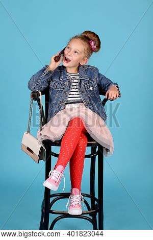 A Little Fashionista Girl Is Sitting In A High Chair With A Handbag, Talking On The Phone. Striped T