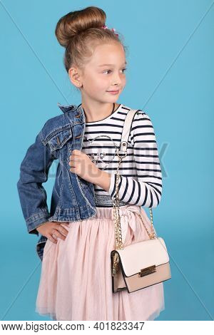 Little Fashionista With A Handbag Posing On A Blue Background. Striped T-shirt With Denim Jacket, Sk