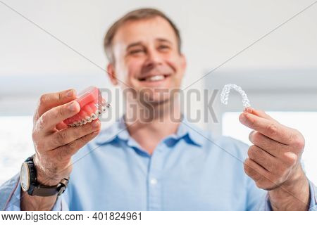 Dental Care.smiling Dentist Doctor Holding Aligners And Braces In Hand Shows The Difference Between