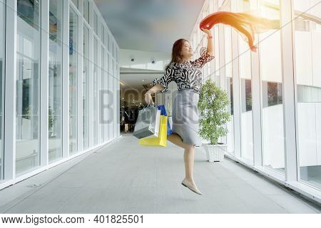 Asian Women Carry Colorful Paper Bags From Shopping. She Jumped Happily As She Had Bought The Items