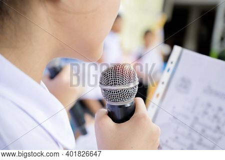 A Girl Holding A Microphone Singing A Song With The Band, With The Music Notes. She Is Very Happy Wi