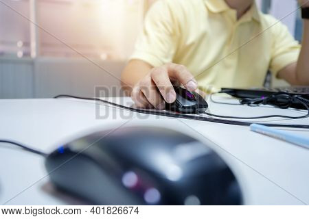 A Young Asian Businessman Is Working In The Office. The Hand That Holds The Mouse To Do The Computer