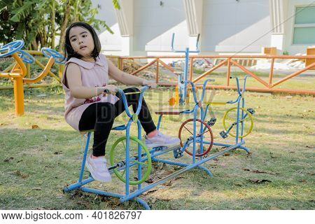 An Asian Girl Is Playing On A Playground. She Is Riding A Bicycle Alone.