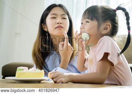 Asian Sisters And Sisters, They Are Happily Eating Cakes. The Place In The Living Room Has A Sofa An