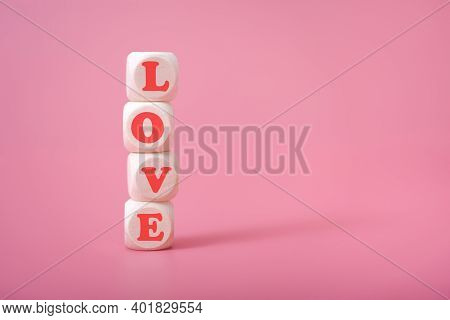 The Word Love Is In The Shape Of A Heart On Wooden Cubes On A Pink Background.