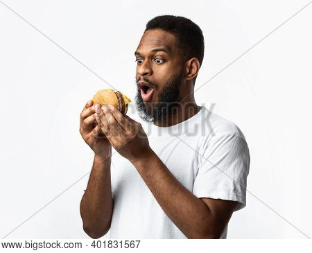 Excited Black Man Holding Unhealthy Burger Posing Standing On White Studio Background. Junk Food Eat