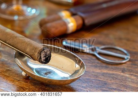 Cigar On An Ashtray, Wooden Table, Closeup View.