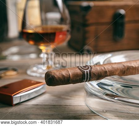 Cuban Cigar In An Ashtray On Wooden Desk