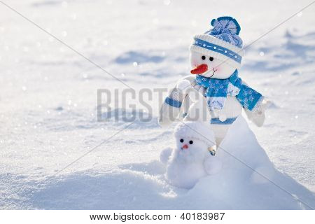 Two snowman on a snowy background.