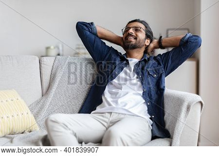 Relaxed Smiling Arab Guy Leaning Back On Couch At Home, Relaxing After Successful Day, Positive Youn