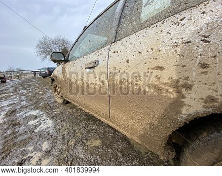 The Detail Of The Car Completely Dirty By Mud After The Drag Race On A Field During Winter. It Needs