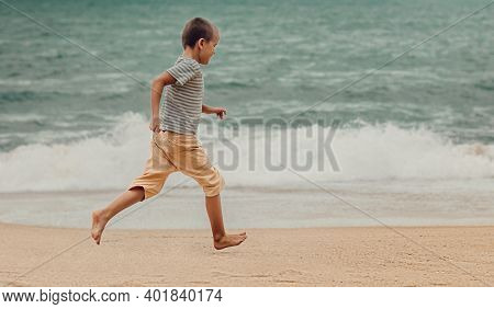 Outdoor portrait of a little cute boy running on a beach