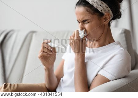 Closeup Ofs Ick Young Woman Sitting On Couch And Sneezing, Measuring Body Temperature, Home Interior