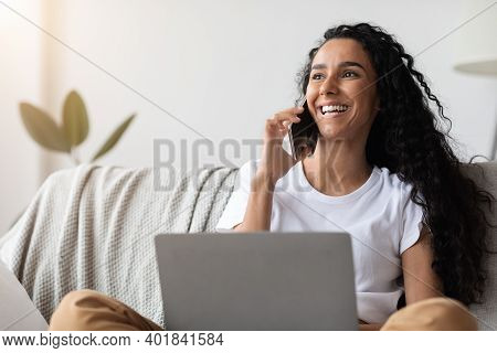 Cheerful Young Woman Freelancer Talking On Mobile Phone And Using Laptop, Working From Home During I
