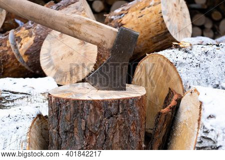 Ax Stuck In The Stump. Stump And Ax In Winter Weather. Felled Tree. Preparing Firewood For Winter.