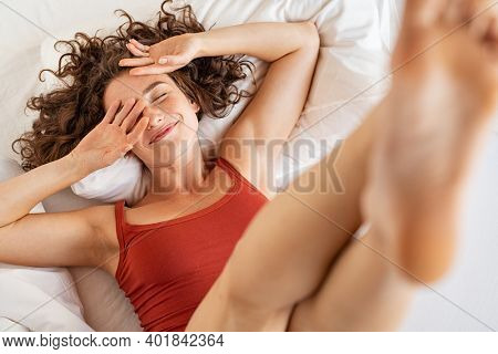 Top view of young happy woman lying on bed while lifting legs up. High angle view of beautiful girl enjoying her waking up. Happy smiling woman lying and stretching in early morning.