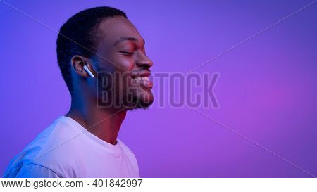 Relaxed African American Man Listening Music In Wireless Airpods Earphones In Neon Light, Smiling Bl