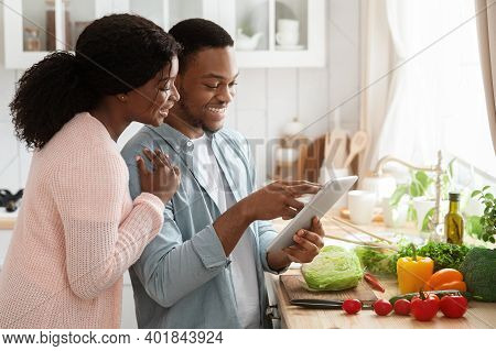 Smiling Black Couple Using Digital Tablet While Cooking Together In Kitchen, Searching Recipe Online