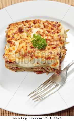 Homemade lasagne verdi on a white plate with a fork, vertical orientation poster