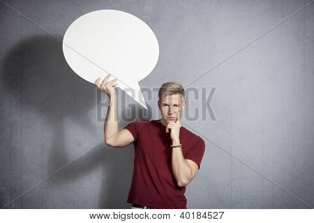 Questioning man  holding white blank speech bubble with space for text isolated on grey background.