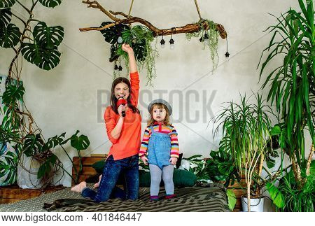 Modern Lifestyle. Exotic Houseplants.family Relaxation Activities Concept. Sisters Are Both Singing
