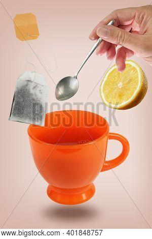 Female's Hand Holding Steel Spoon With Levitating Orange Teacup, Tea Bag, And Lemon Over The Pink Su